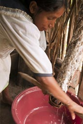 Applying and winding of mats of interwinded palm strings, and the indigena woman dehydrates the yuca grate. Water is being reused in soups. Making of Yuca bread. Ecuador, Amazon basin. Cuyabeno.