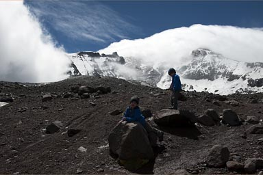 Twin boys raise arms, Chimborazo glacier and blue skies.