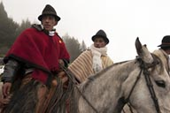 Men on horses and in ponchos gather in fog in Salinas, Ecuador.