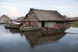 In Iquitos, flaoting home, family, clothes washing, men in boat. Peruvian Amazonas River.