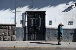 Woman walks by, white house street Cajamarca.