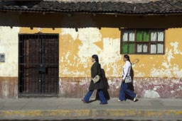 Morning sun on orange house, two young ladies walk by, Cajamarca, Peru.
