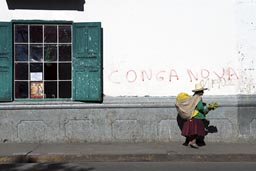 Conga no va! on house in Cajamarca. Indigenas woman with pack and hat walks by.