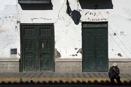 Cajamarca, morning, a man sits on side walk.