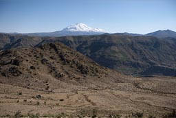 Snow capped Ampato volcanoe sticks out over Andean landscape.