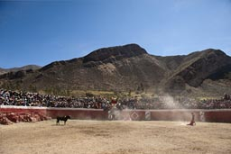 Mountains, bull fighting arena in Huambo, packed with local people. Peru.