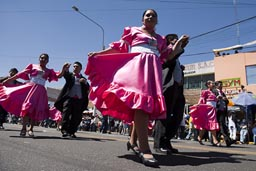 Ladiesin rose, men in black, couples dance down the street o Arequipa Day.