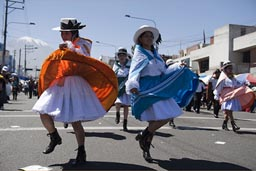 Traditional dresses from all regions, red and blue dance down Independence Avenida, Arequipa Day Peru.