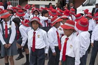 On a Sunday, parading in Huancayo, kids and red hats.
